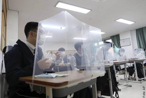 Foto de estudiantes en sus pupitres con cabinas separadoras