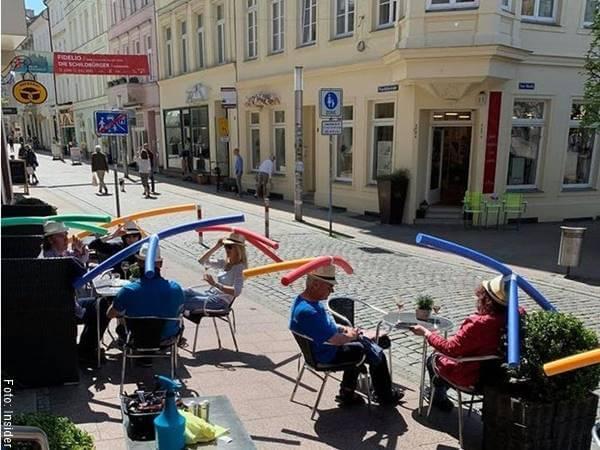 Fotos de personas con sombreros que toman distancia sentados en un café