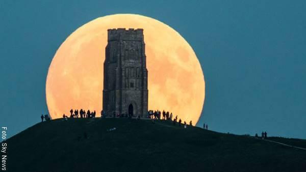 Foto de una luna llena detrás de una torre de piedra