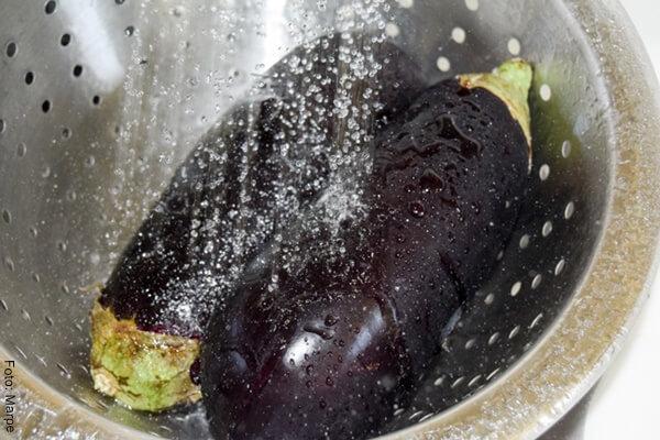 Foto de dos berenjenas en un recipiente cayéndoles agua