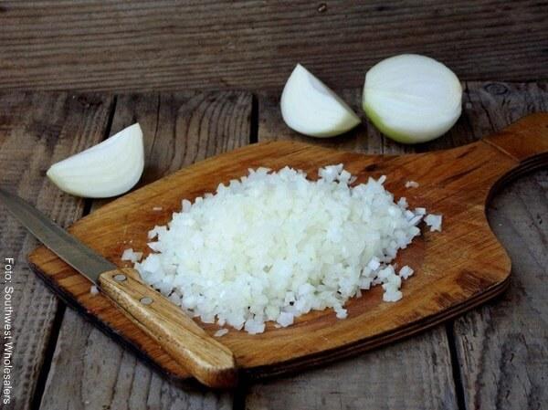 Foto de cebolla cabezona picada en cuadritos encima de una tabla de picar con un cuchillo