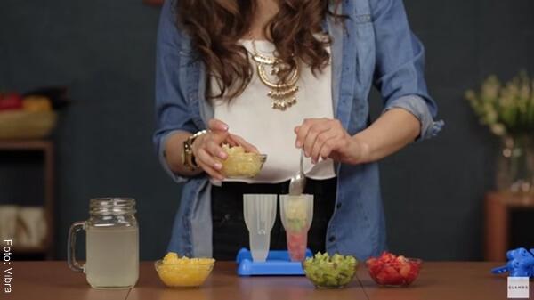 Foto de una mujer rellenando unos moldes de paleta con fruta picada