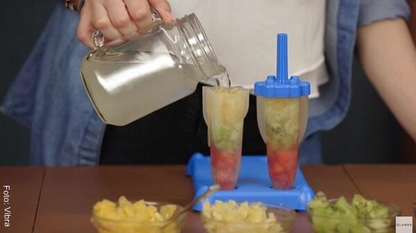 Foto de la mano de una mujer añadiendo limonada en moldes para paleta