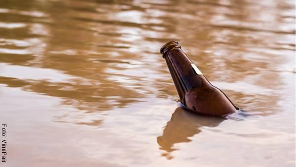 Foto de agua sucia con una botella flotando