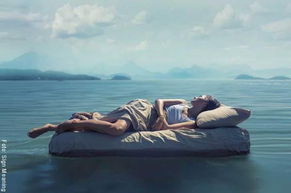 Foto de una mujer en un colchón flotando sobre el agua
