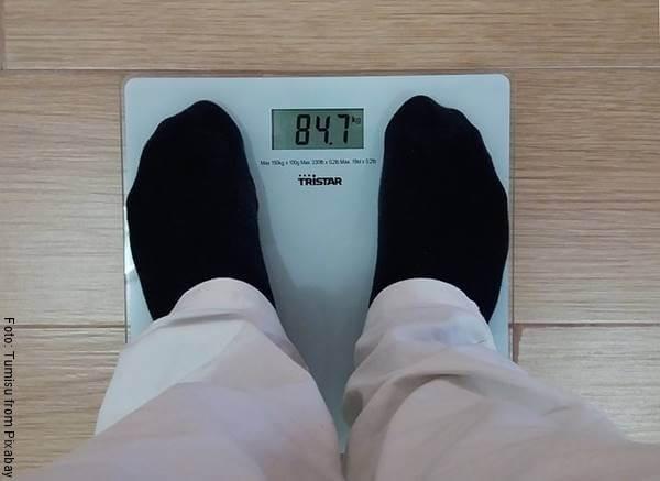 Foto de un hombre pesándose en una báscula