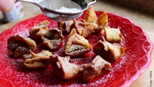 Foto de frituras en un plato rojo con azúcar en polvo