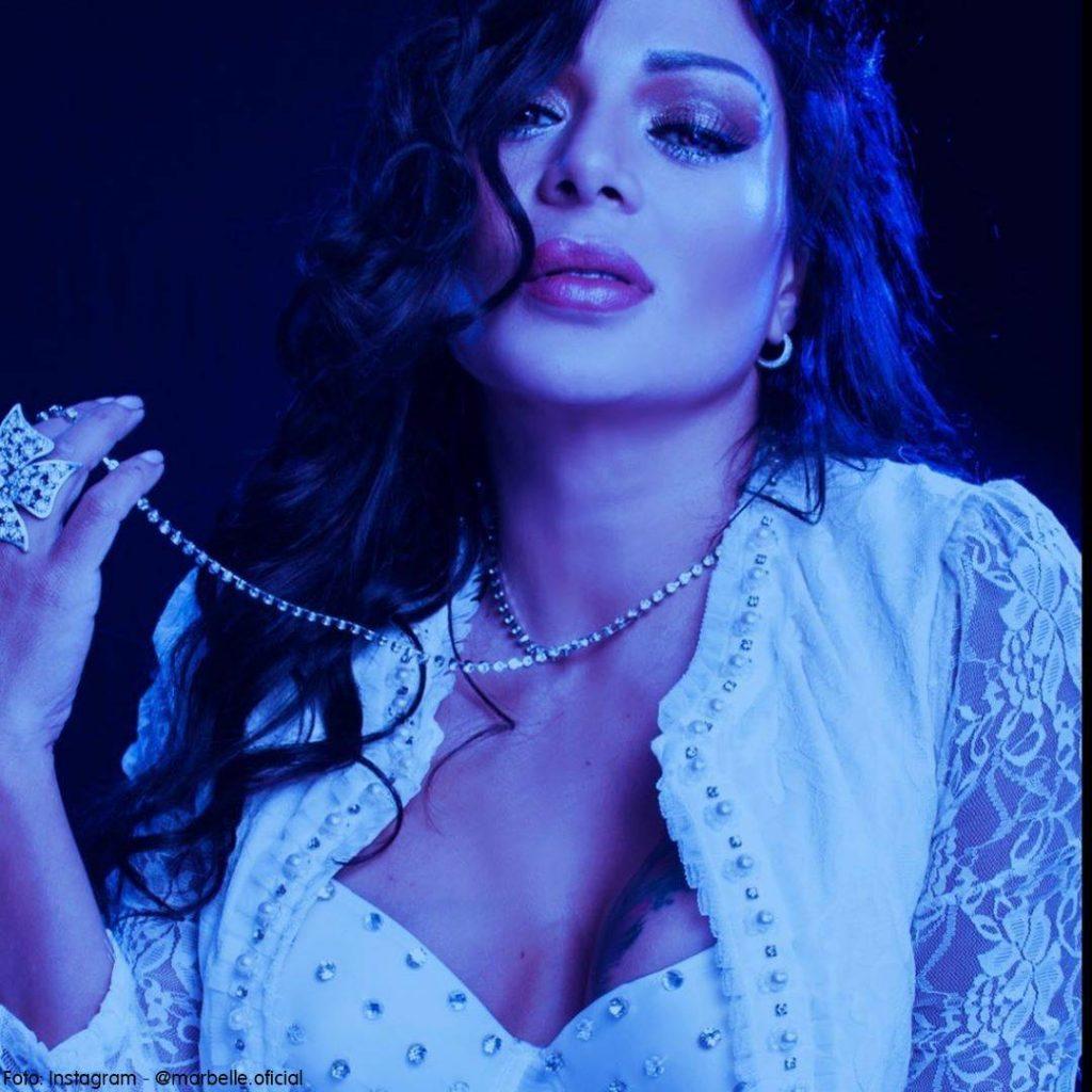 Foto de Marbelle con un fiiltro azul y un collar en la mano