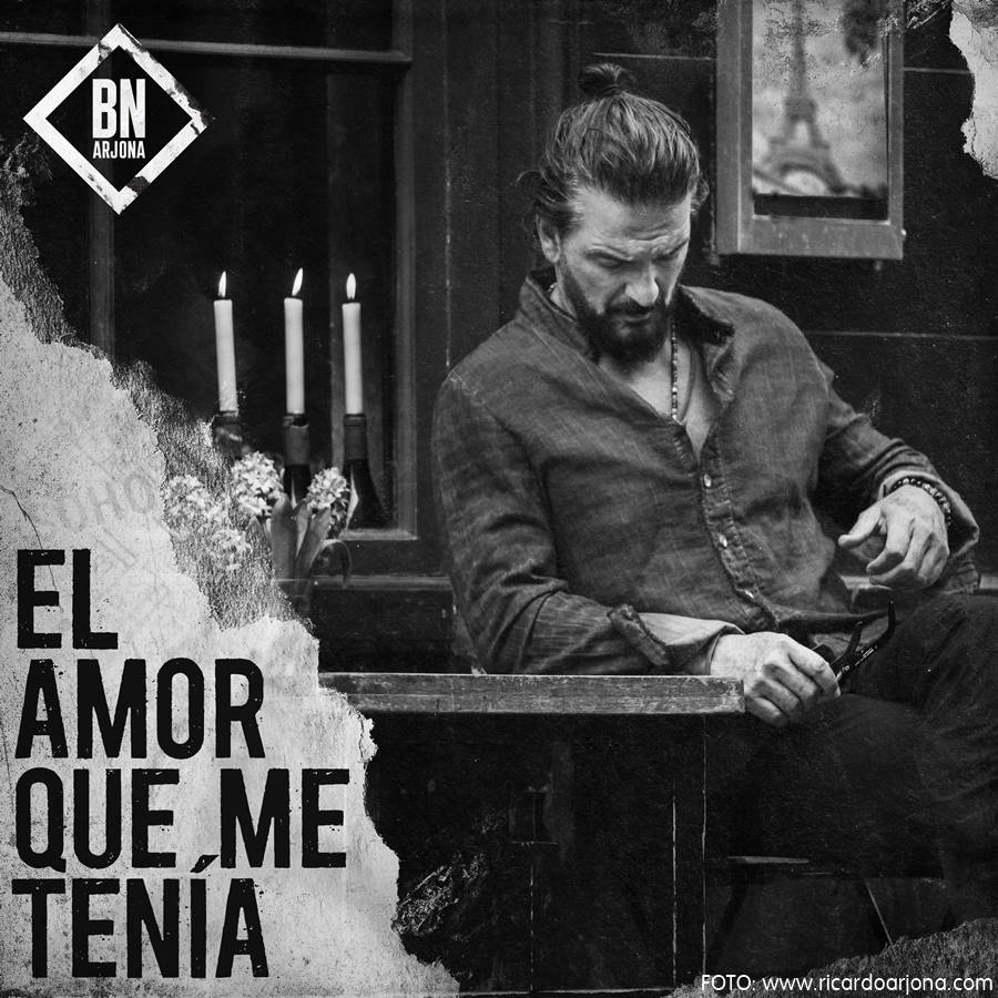 Ricardo Arjona sentado en la mes de un bar, portada de su nuevo sencillo