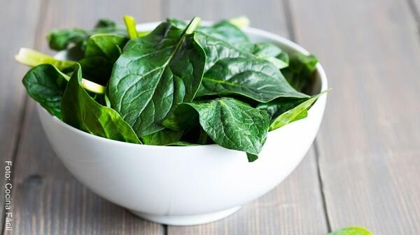 Foto de hojas de espinacas frescas en un recipiente blanco