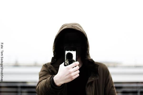 Foto de un hombre con capucha al que no se le ve es rostro tomándose una foto