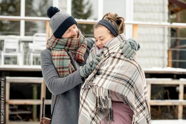 Foto de un hombre abrigando a una mujer con una manta