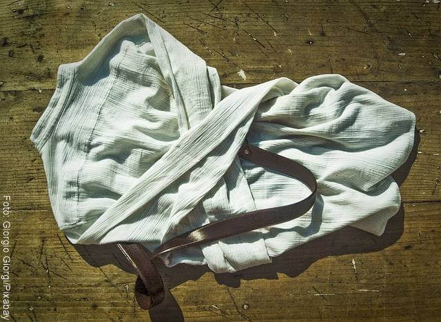 Foto de una camisa en el suelo con un cinturón