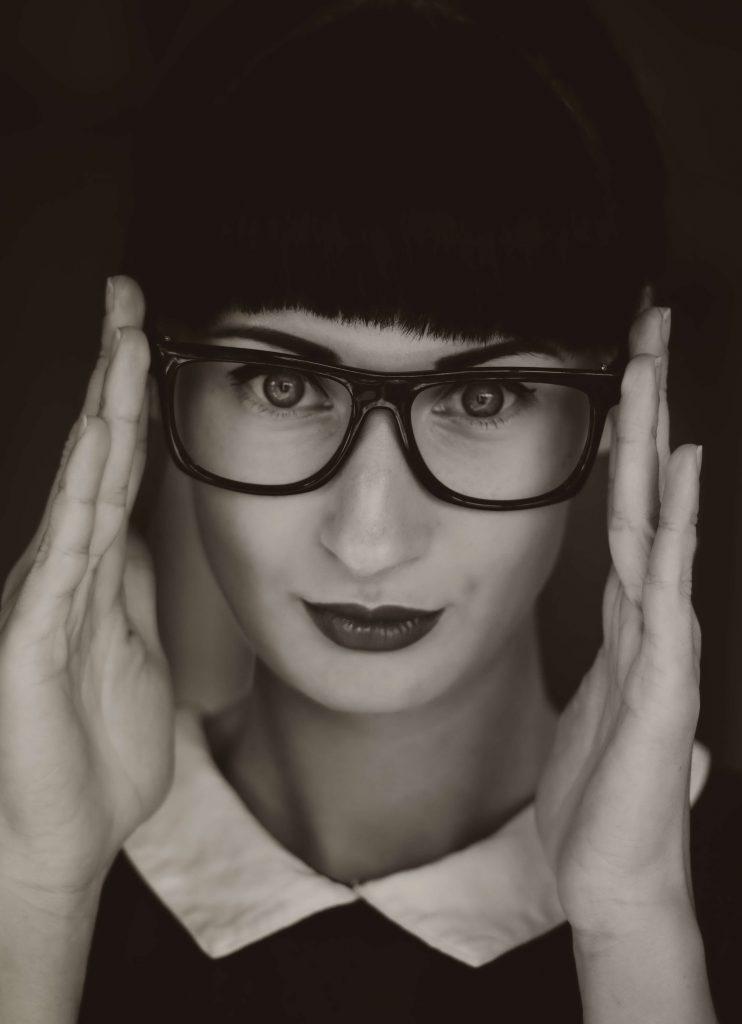 Foto de una mujer con gafas en blanco y negro para ejemplificar qué beneficios tiene el café