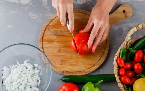 Foto de las manos de una señora cortando un tomate sobre una tabla de madera