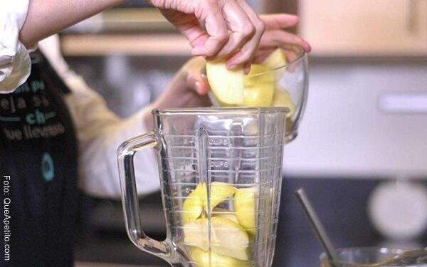 Foto de las manos de una persona agregando manzanas en trozos a una licuadora