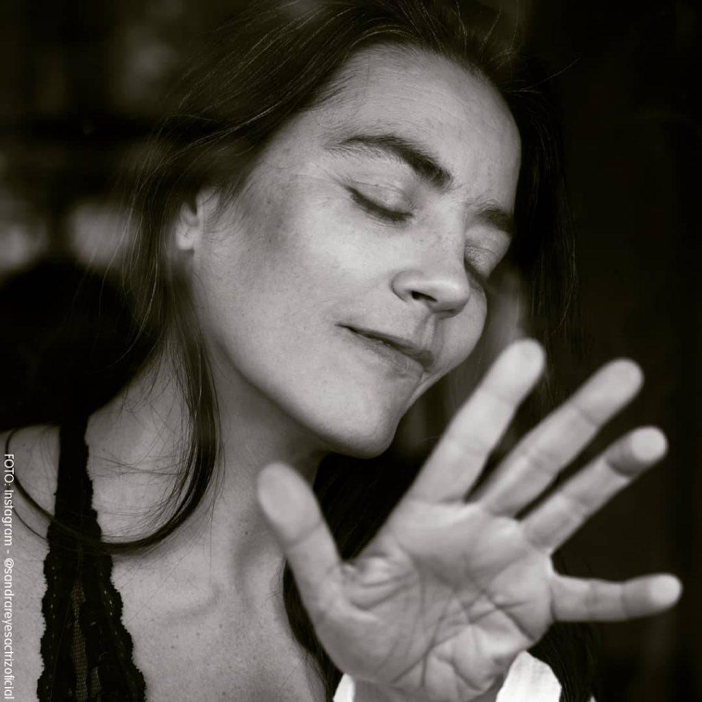 Sandra Reyes intentando tapar su rostro con su mano