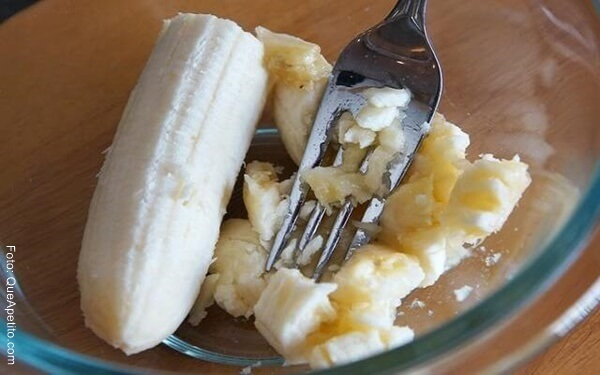 Foto de un banano triturado con un tenedor dentro de un recipiente
