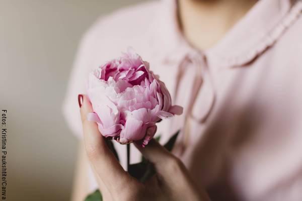 Foto de una mujer con una flor entre las manos