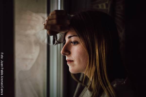 Foto de una mujer mirando por una ventana
