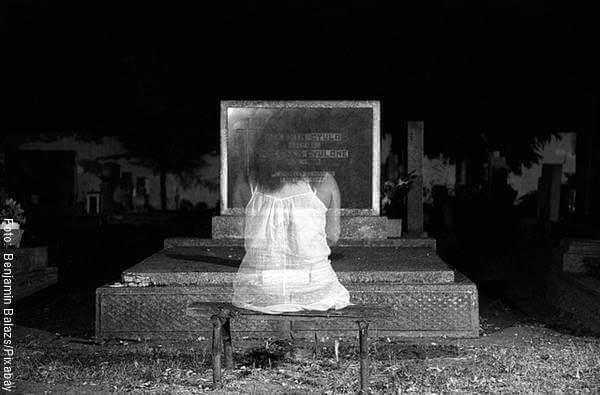 Foto de una mujer frente a una tumba