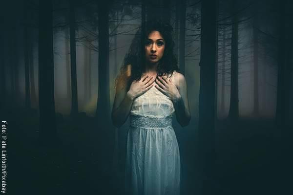 Foto de una mujer asustada en el bosque