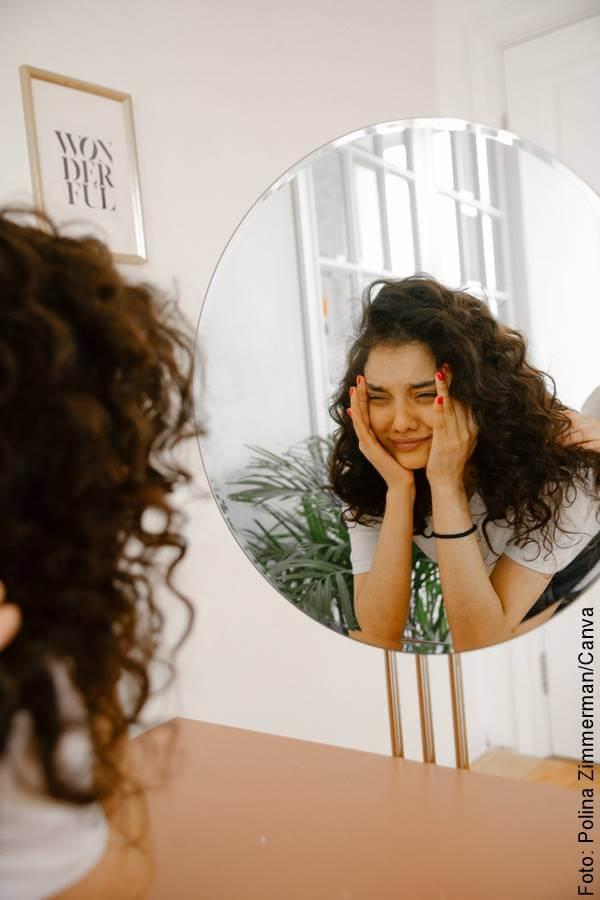 Foto de chica angustiada mirándose al espejo