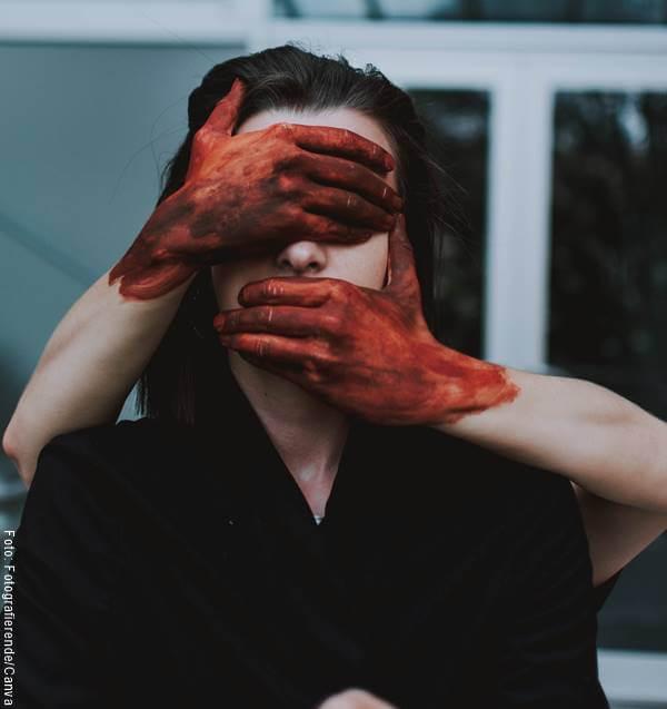 Foto de una mujer a la que le están tapando los ojos y la boca con manos ensangrentadas