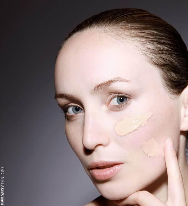Foto de mujer aplicándose base en el rostro