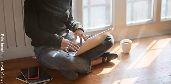 Foto de una persona con un portátil en sus piernas