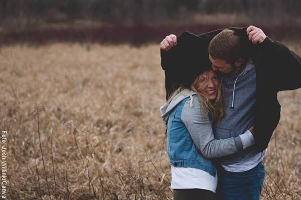 Foto de una pareja bajo la lluvie en el campo