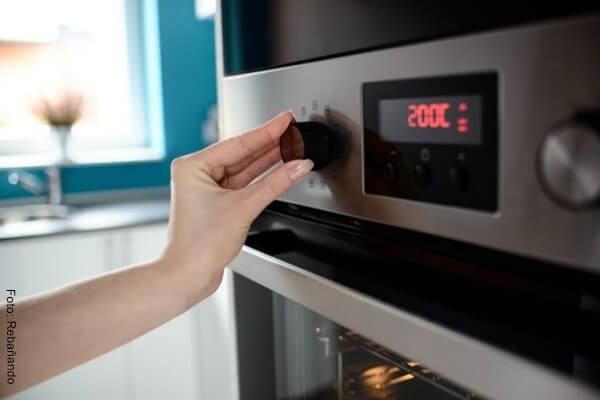 Foto de la mano de una mujer colocando a precalentar un horno