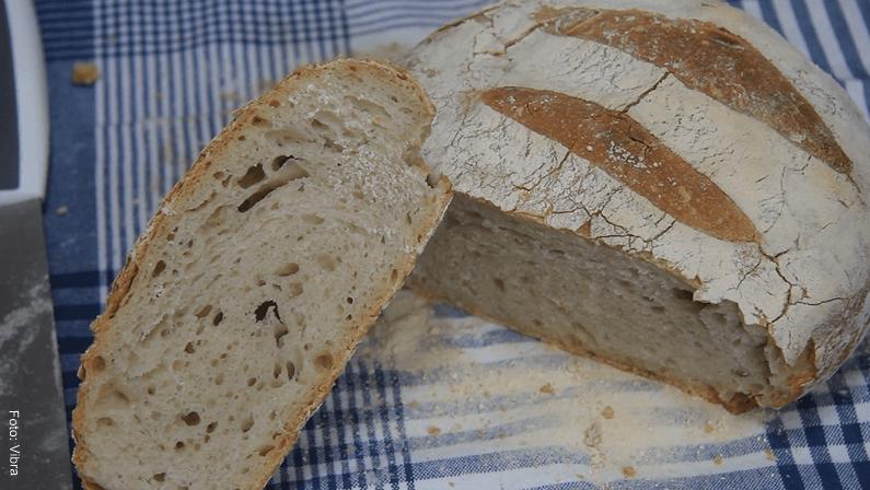 Foto de un pan casero y crujiente partido por la mitad