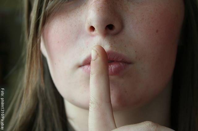 Foto detalle de los labios de una mujer callando con el dedo