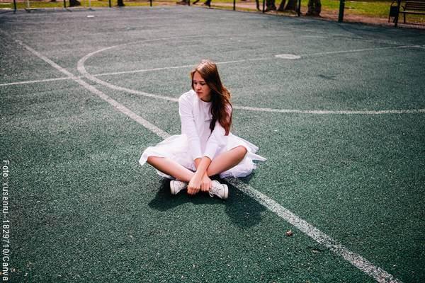 Foto de una chica sentada en una cancha