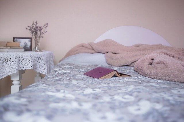 Foto de una cama vacía con un libro encima para ilustrar cuánto tiempo hay que dormir según la edad
