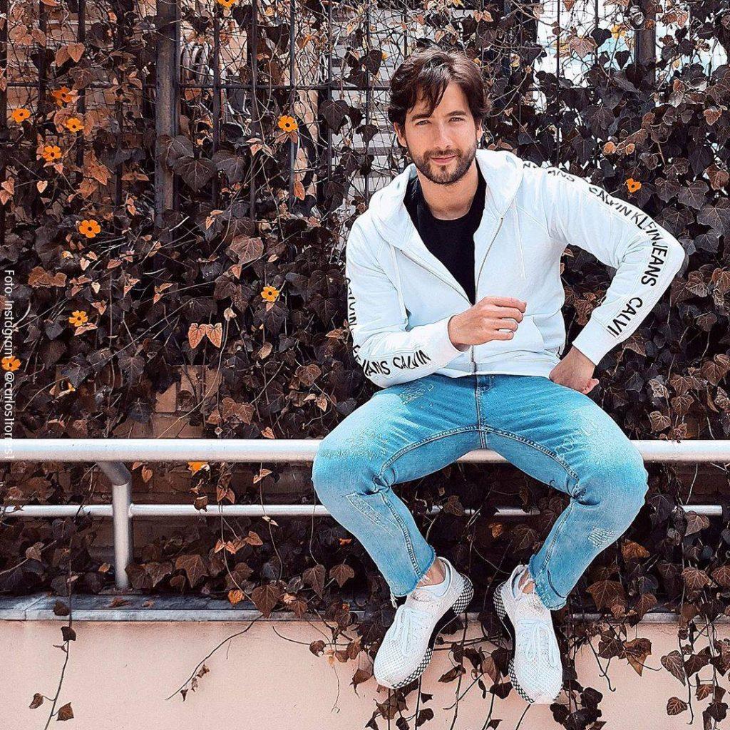 Foto de Carlos Torres sentado en una baranda con una chaqueta blanca y jean azul