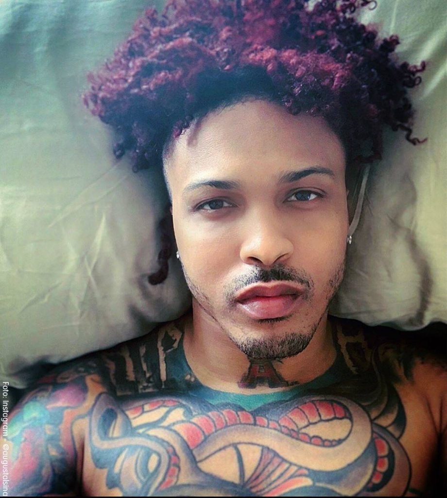 Foto de August Alsina luciendo sus tatuajes recostado en la cama