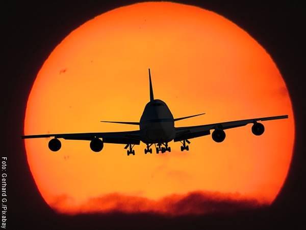 Foto de la silueta de un avión con el sol de fondo