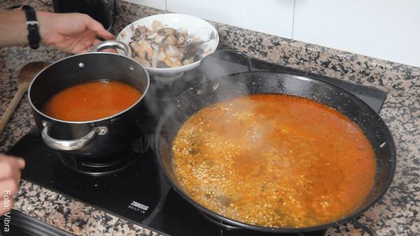 Foto de arroz para paella con agua en un sartén