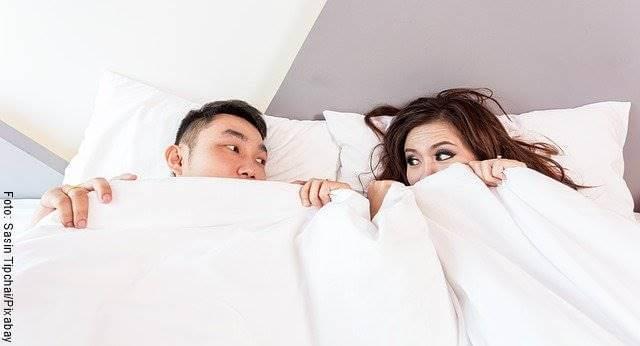 Foto de una pareja entre las sábanas