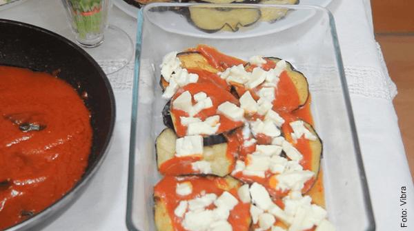 Foto de rodajas de berenjenas con salsa de tomate y queso dentro de una refractaria