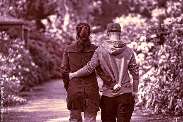Foto de una pareja de espaldas, caminando y abrazados