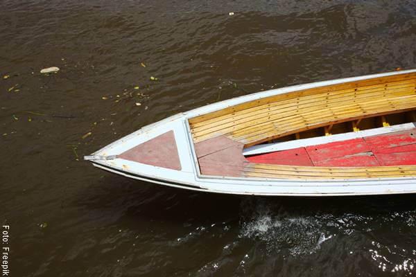 Foto de una lancha en un río sucio
