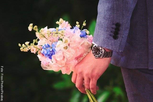 Foto de un hombre con un ramo de flores en la mano