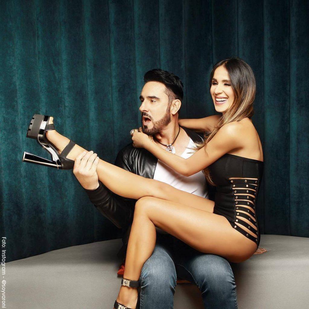 Foto de Miguel Varoni y Catherine Siachoque sentada en sus piernas con un corset negro