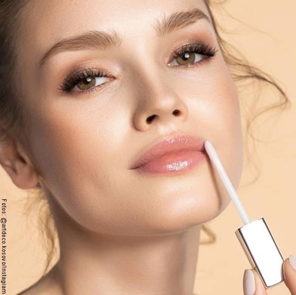 Foto de una chica aplicándose brillo labial