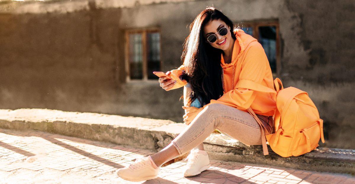 Foto de una mujer sentada en un andén y su smartphone en la mano