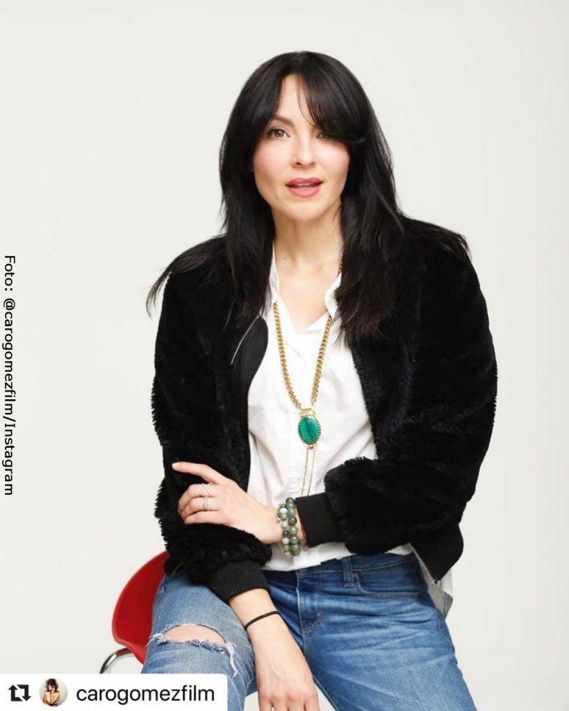 Carolin Gómez luciendo un saco lanudo negro, camiseta blanca y jeans rotos durante una sesión de fotos.
