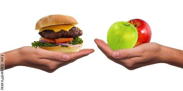 Foto de dos manos, una con una hamburguesa y la otra con manzanas